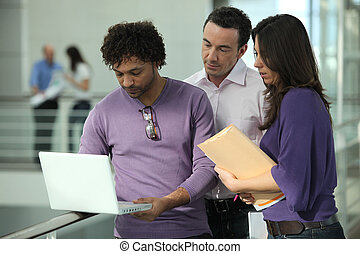 Colleagues looking at a laptop