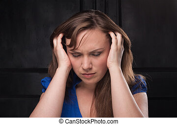 Girl with headache on dark background - She clasped head in...
