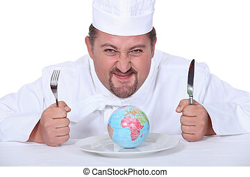 Chef sat with miniature globe on plate