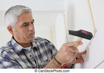 Grey-haired man repairing house