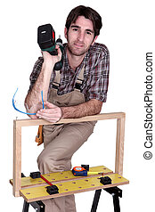 Man posing with his workbench and holding an electric...