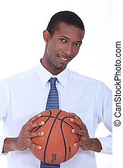 young black man well dressed taking a basket ball