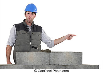 Shocked builder stood by wall pointing