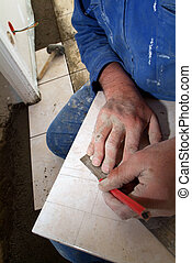 Manual worker measuring a tile