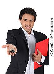 Estate-agent handing over keys to house