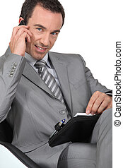Confident male executive with mobile phone and diary