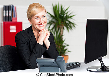Aged businesswoman sitting with hands on chin