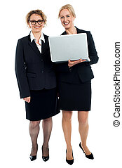Senior businesswomen posing with laptop