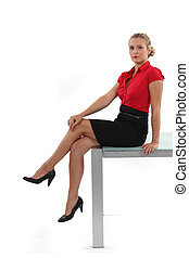 Attractive blond sat on desk