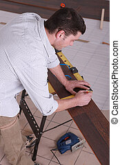 Man taking measurements on a workbench