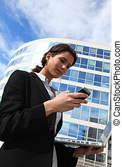 Woman texting on a mobile phone outside an office building