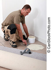 Carpet fitter spreading adhesive on a tiled floor