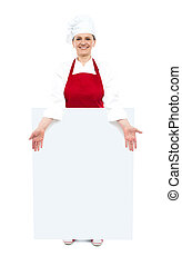 Female cook showing white blank ad board, full length shot