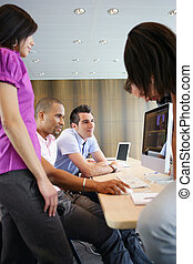 Young people sitting round a computer