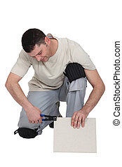 Man cutting tile to right size