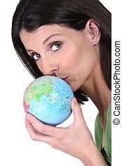 Woman kissing globe