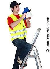 Young laborer on a ladder with spray