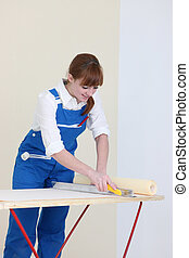 Woman getting ready to hang wall paper