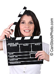 Brunette woman with movie slate
