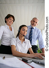 Business people at a laptop with headset