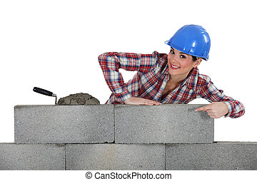 portrait of young female bricklayer pointing at concrete...