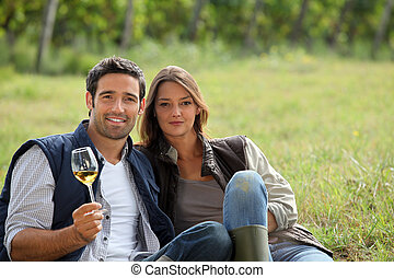 Couple having a glass of wine by a vineyard
