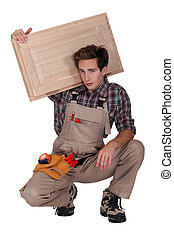 portrait of young cabinetmaker carrying cupboard door over...