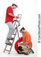 Tradesmen installing copper and corrugated tubing