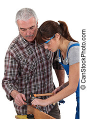 Carpenter teaching young female apprentice