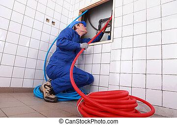 Plumber installing piping