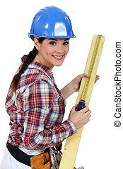 Construction worker measuring a piece of wood