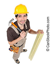 Carpenter with wood and a hammer