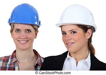 Two woman with their hardhat on.