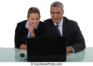 businessman and businesswoman smiling in front of the laptop