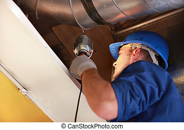 worker examining an attic