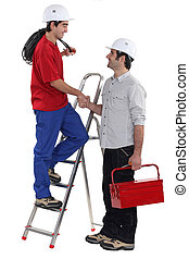 Two manual workers shaking hands