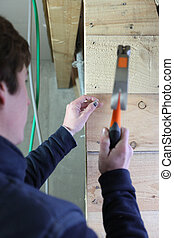 Carpenter nailing a wooden wall