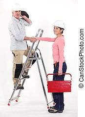 An electrician and his female apprentice.