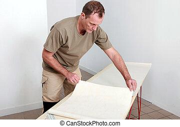 Man laying wallpaper