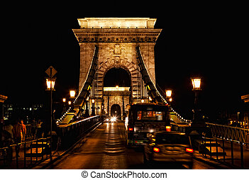 Chain bridge at night with cars