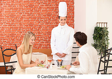 Chef talking to a couple in a restaurant