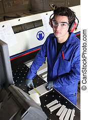 Young factory worker operating cutting machine