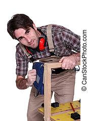 Man sawing through wooden frame