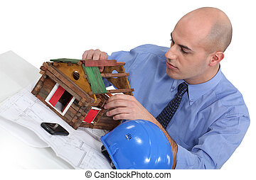 Man building a house model