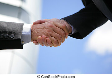 Two businesspeople shaking hands outdoors
