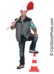 road worker holding a shovel and leaning his foot on a...