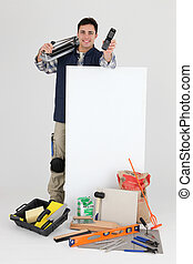 Tradesman holding a mobile phone over a blank sign and his...