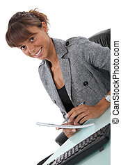 Happy office worker writing at her desk