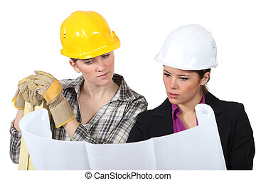 Construction worker looking at a plan with an engineer