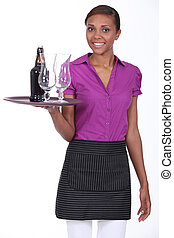 Pretty waitress carrying a bottle of beer and two glasses on...